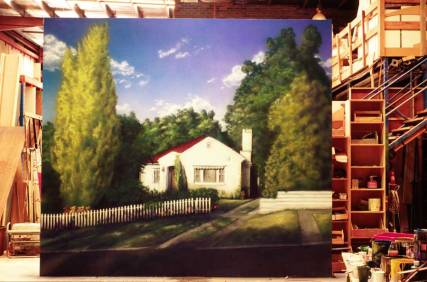 Large painted canvas of house and trees inside a workshop